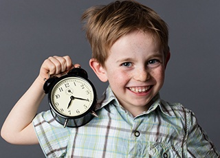 Little boy holding clock