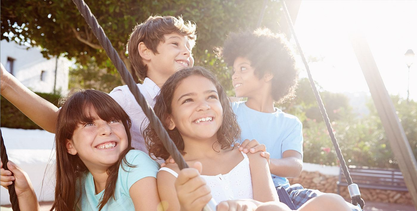 Four smiling kids playing outdoors
