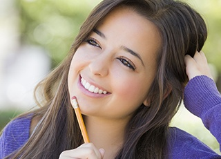 Smiling girl holding pencil